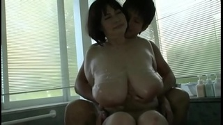 Mature beautiful Asian with big tits fucks with a young man